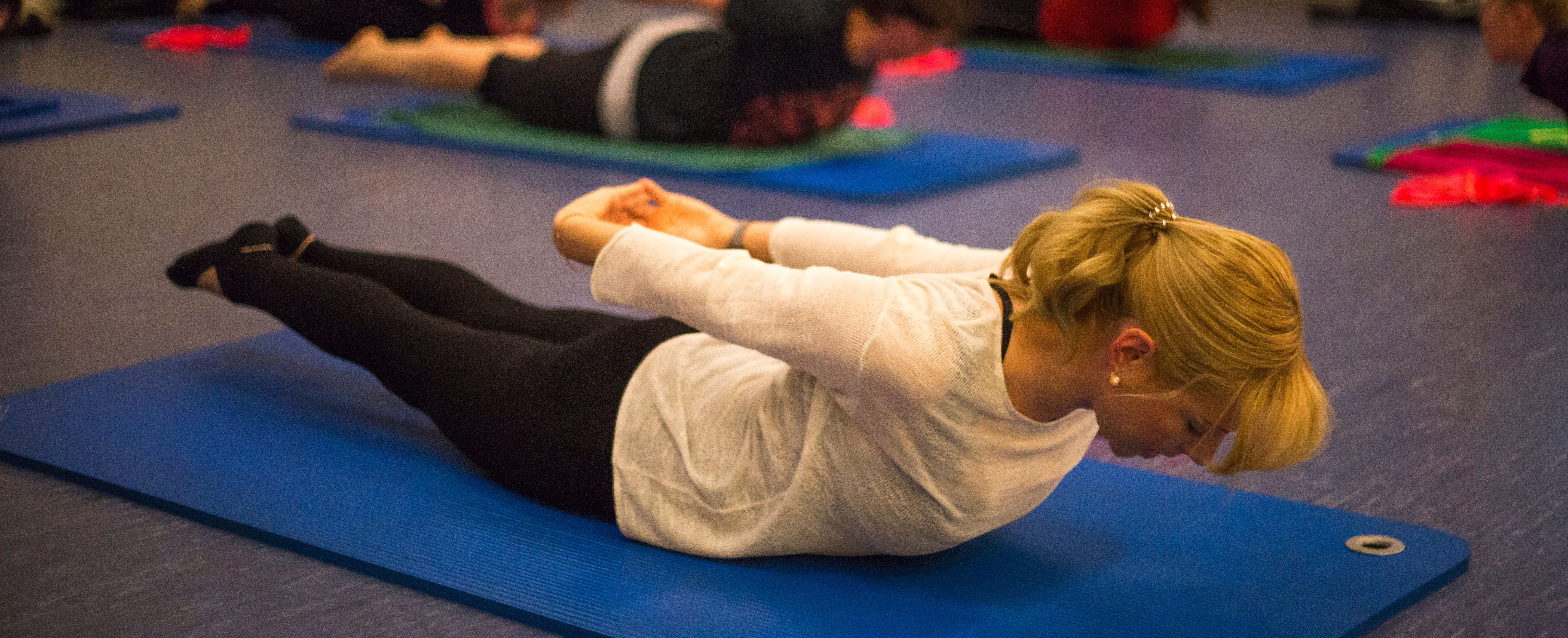 Teacher demonstrating a pilates exercise