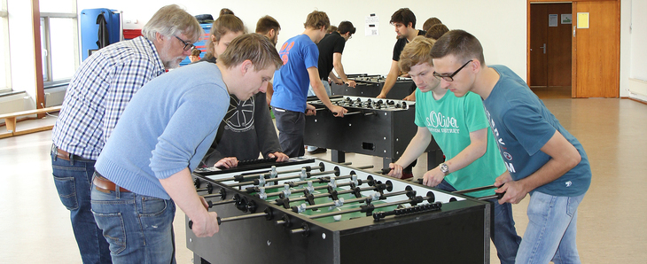 4 people playing table soccer