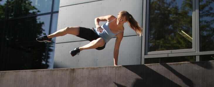Woman jumping over concrete wall