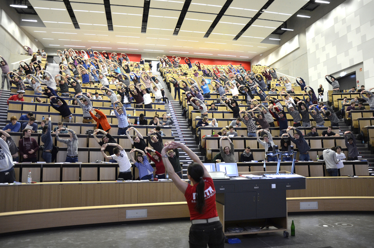 people making sports in an auditorium