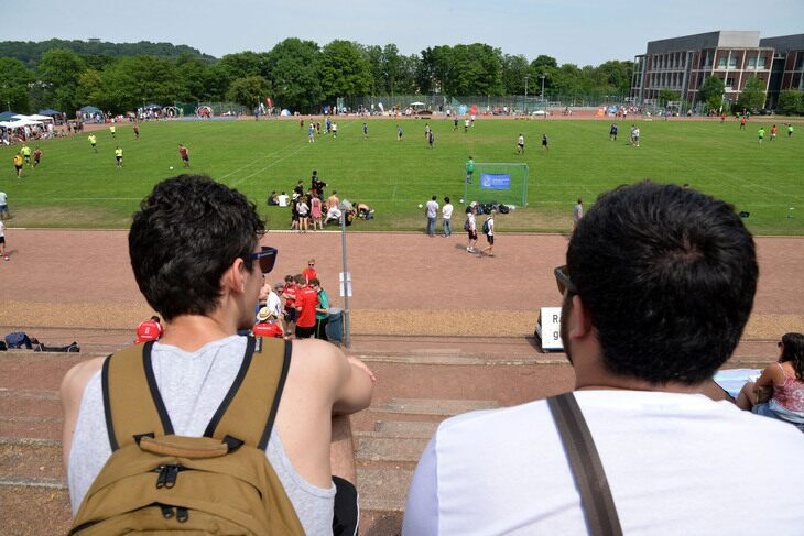 Two people sitting with a sports field in front of them