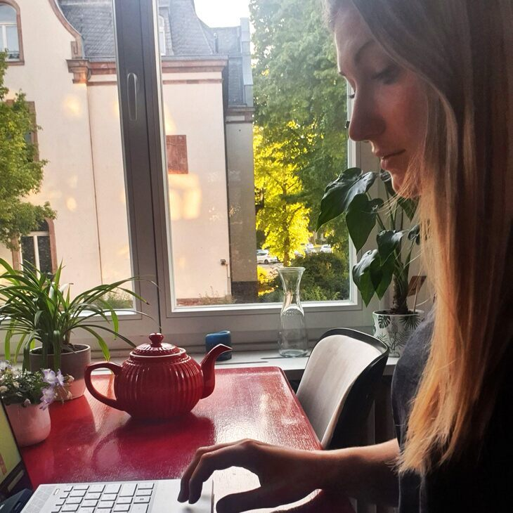 Woman using a laptop infrot of a window