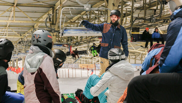 Skiing Instructors explains something to a group in a skihall.